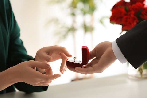 Young man proposing to his beloved at romantic date