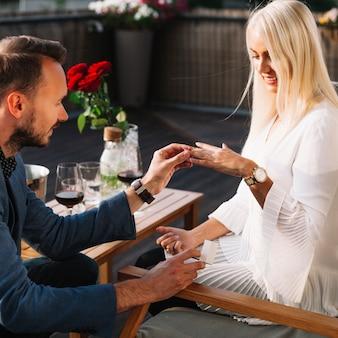 Young man proposing to smiling beautiful woman outdoors