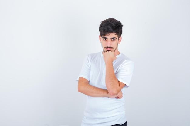 若い男はtシャツの拳で顎を支え、自信を持って見える