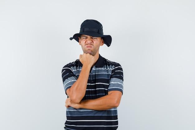 Молодой человек подпирает подбородок поднятым кулаком в футболке, шляпе и выглядит безрадостным. передний план.