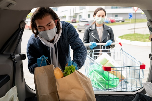 Young man in protective gloves and mask putting paperbags with food products into car trunk