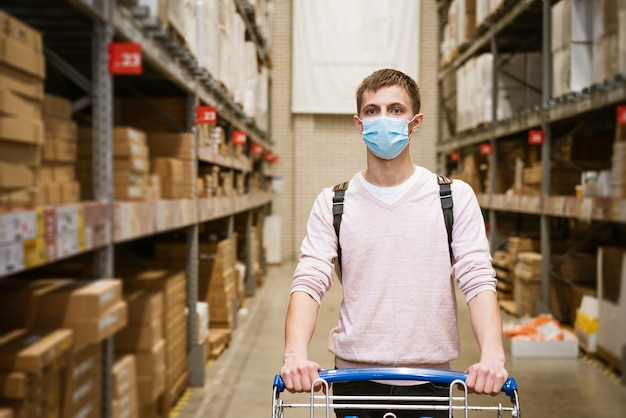 Young man in a protective mask in casual clothes with a trolley in a store warehouse