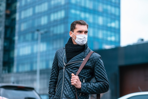 Young man in a protective mask standing on the street