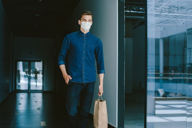 Young man in a protective mask walking along a city street. coronavirus in the city