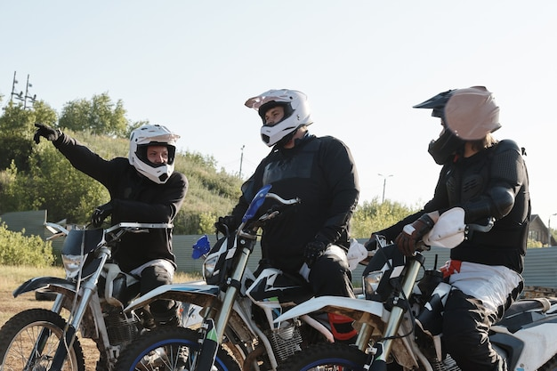 Young man in protective wear and helmets showing direction while discussing motorcycle track with friends