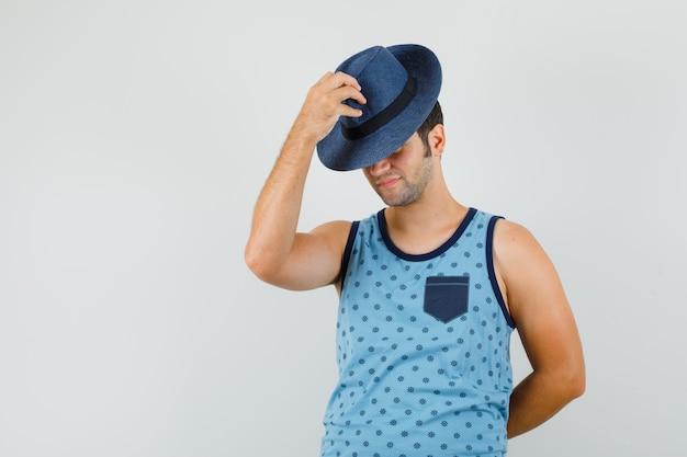 Giovane che tira giù il cappello sugli occhi in singoletto blu e sembra elegante. vista frontale.