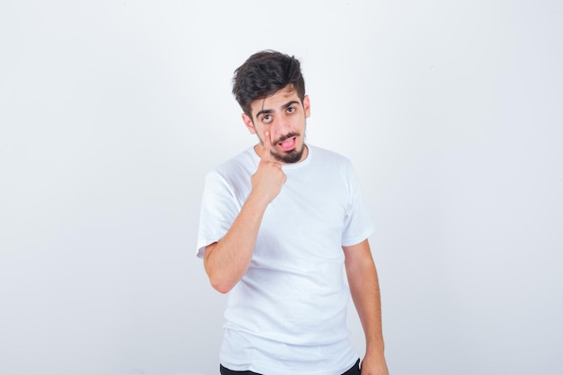 Молодой человек опускает веко в белой футболке и выглядит уверенно