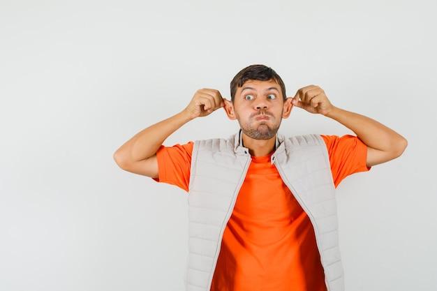Молодой человек тянет за уши пальцами, надувает щеки в футболке, куртке и выглядит смешно