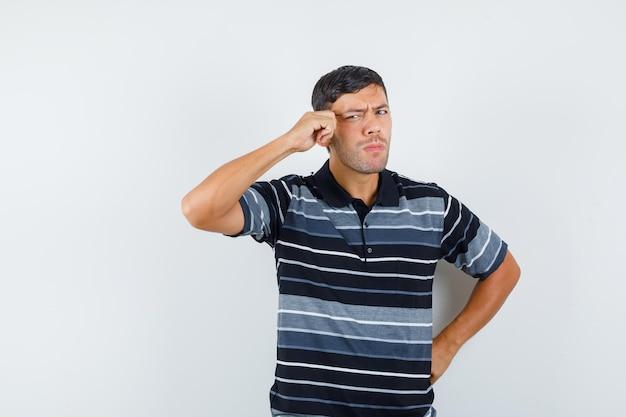 Молодой человек в футболке натягивает кожу на висках и выглядит серьезным. передний план.