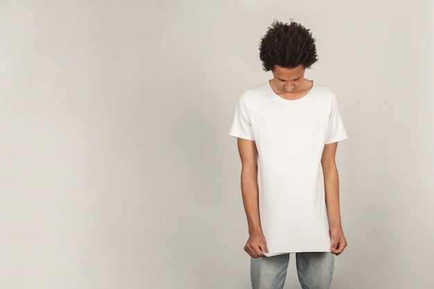 Young man pulling on t-shirt