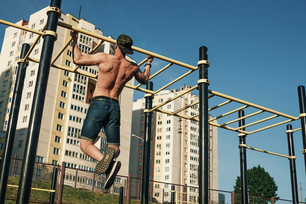 A young man pulls himself up sports ground, an athlete, training outdoors in  city