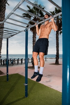 Young man pullups exercise routine outdoor
