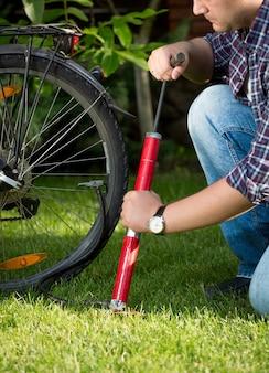 공원에서 자전거 타이어를 펌핑하는 젊은 남자