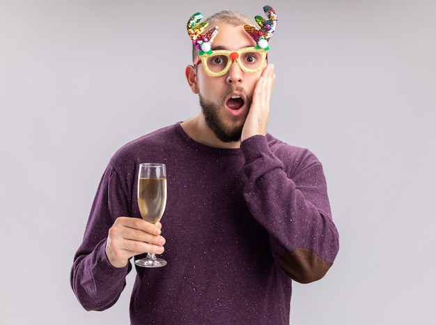 Young man in purple sweater and funny glasses holding glass of champagne looking at camera amazed and surprised standing over white background