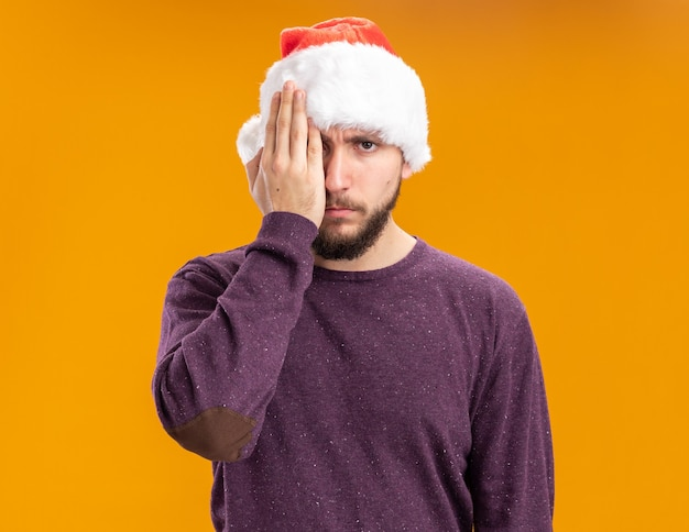 Giovane uomo in maglione viola e cappello da babbo natale che copre un occhio con la mano in piedi su sfondo arancione