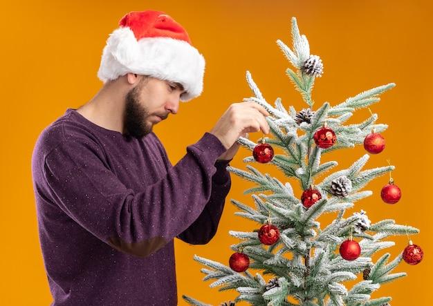 Giovane uomo in maglione viola e cappello da babbo natale appesi giocattoli sull'albero di natale con la faccia seria in piedi su sfondo arancione