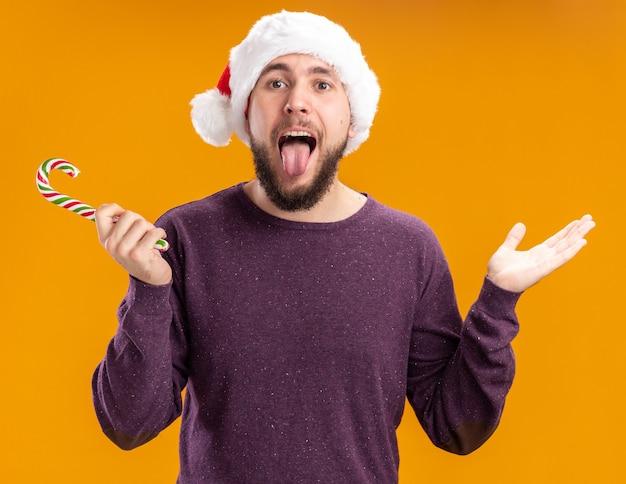 Giovane uomo in maglione viola e cappello della santa che tiene il bastoncino di zucchero che guarda l'obbiettivo che attacca fuori linguetta felice e allegra in piedi su sfondo arancione