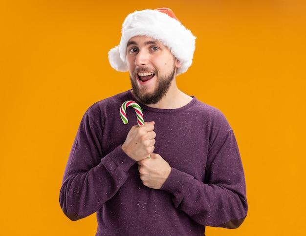 Giovane uomo in maglione viola e cappello santa tenendo il bastoncino di zucchero guardando la fotocamera con la faccia felice sorridente in piedi su sfondo arancione