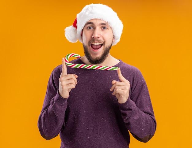 Giovane uomo in maglione viola e cappello santa tenendo il bastoncino di zucchero guardando la fotocamera con la faccia felice in piedi su sfondo arancione