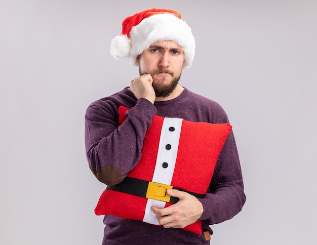 Young man in purple sweater and santa hat holding funny pillow looking at camera displeased standing over white background