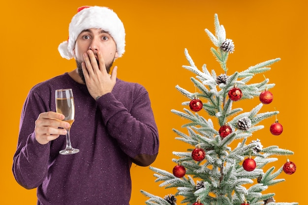 Young man in purple sweater and santa hat holding glass of champagne  amazed and surprised standing next to christmas tree over orange wall