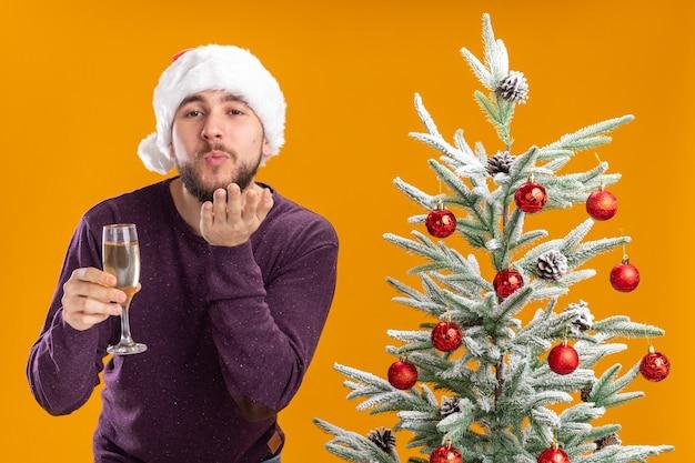 Giovane uomo in maglione viola e cappello santa tenendo un bicchiere di champagne accanto all'albero di natale su sfondo arancione