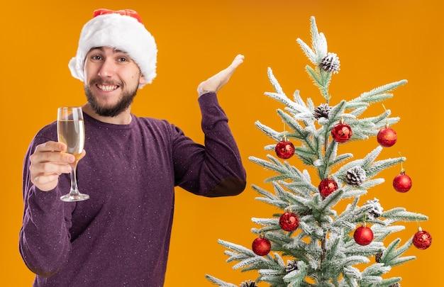 Giovane uomo in maglione viola e cappello santa tenendo un bicchiere di champagne guardando la fotocamera sorridente accanto all'albero di natale su sfondo arancione
