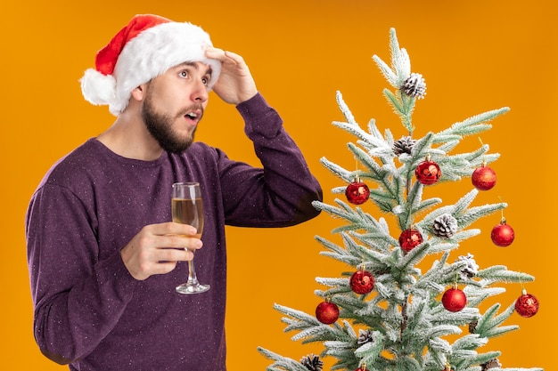 Young man in purple sweater and santa hat holding glass of champagne standing next to christmas tree looking up puzzled over orange wall