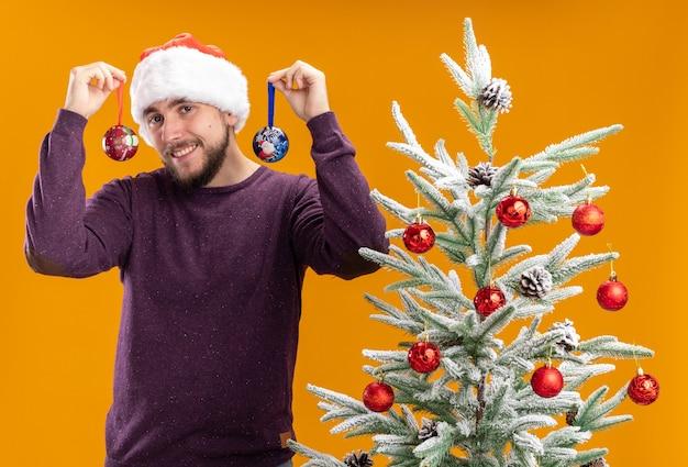 Giovane uomo in maglione viola e cappello santa tenendo i giocattoli guardando la fotocamera con la faccia felice sorridente in piedi accanto all'albero di natale su sfondo arancione