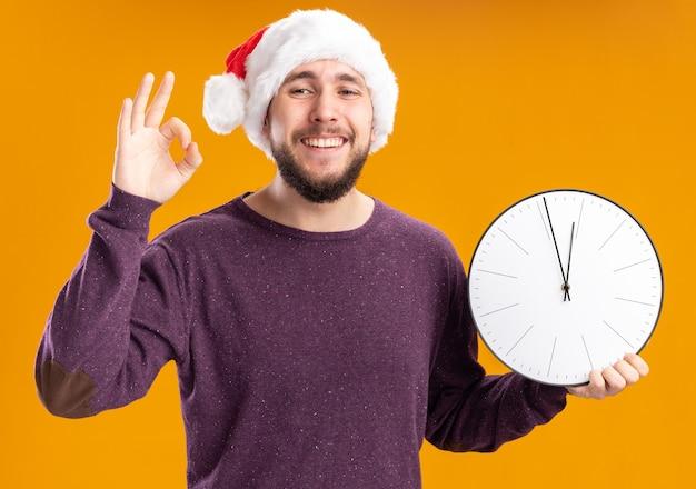 Giovane uomo in maglione viola e cappello santa tenendo l'orologio da parete felice e allegro che mostra segno giusto sorridente in piedi sopra la parete arancione