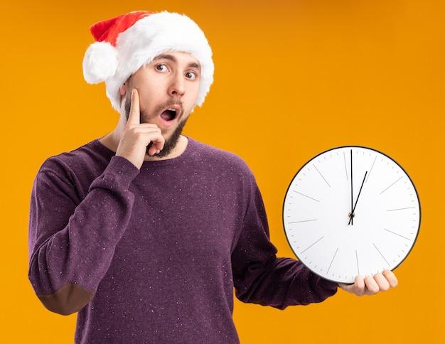 Giovane uomo in maglione viola e cappello da babbo natale tenendo l'orologio da parete guardando stupito e sorpreso in piedi su sfondo arancione