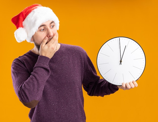 Young man in purple sweater and santa hat holding wall clock looking at it amazed and surprised covering mouth with hand standing over orange background