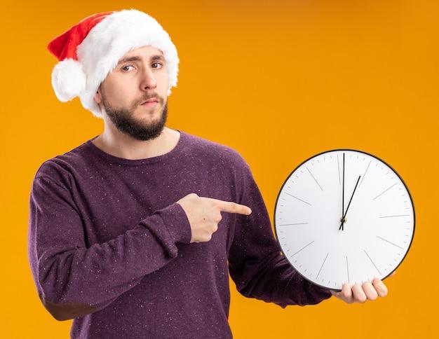 Giovane uomo in maglione viola e cappello da babbo natale tenendo l'orologio da parete che punta con il dito indice guardando la fotocamera con la faccia seria in piedi su sfondo arancione