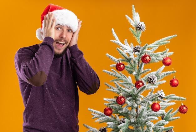Giovane uomo in maglione viola e cappello santa guardando stupito e sorpreso in piedi accanto all'albero di natale su sfondo arancione