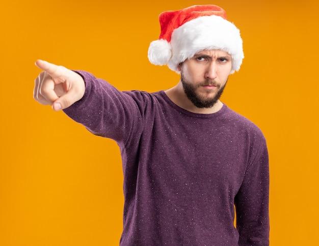 Giovane uomo in maglione viola e cappello da babbo natale guardando da parte con la faccia seria che punta con il dito indice a qualcosa in piedi su sfondo arancione