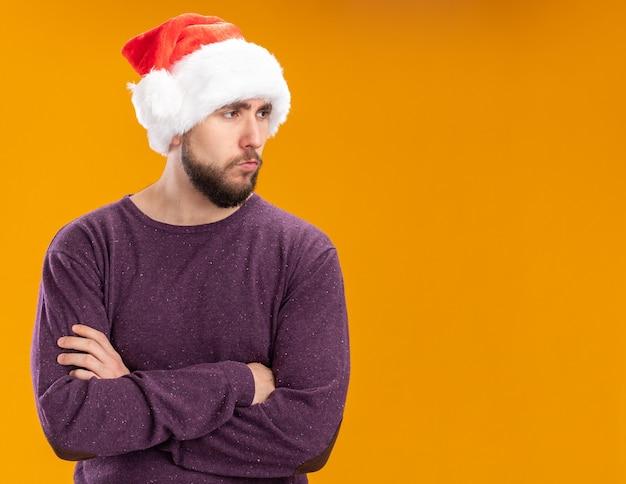 Giovane uomo in maglione viola e cappello da babbo natale guardando da parte con la faccia seria in piedi su sfondo arancione