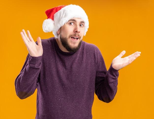 Giovane uomo in maglione viola e cappello da babbo natale che guarda l'obbiettivo confuso scrollare le spalle non avendo risposta in piedi su sfondo arancione