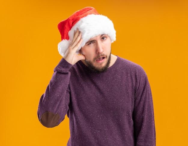 Giovane uomo in maglione viola e cappello da babbo natale che guarda l'obbiettivo confuso con la mano sulla sua testa in piedi su sfondo arancione