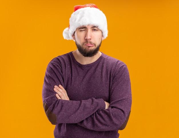 Giovane uomo in maglione viola e cappello santa guardando la telecamera dispiaciuto rendendo la bocca ironica con espressioni deluse in piedi su sfondo arancione