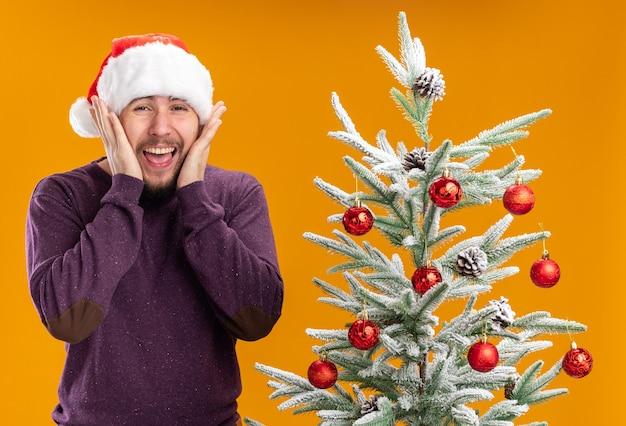 Giovane uomo in maglione viola e cappello santa guardando la fotocamera eccitato e pazzo in piedi felice accanto all'albero di natale su sfondo arancione