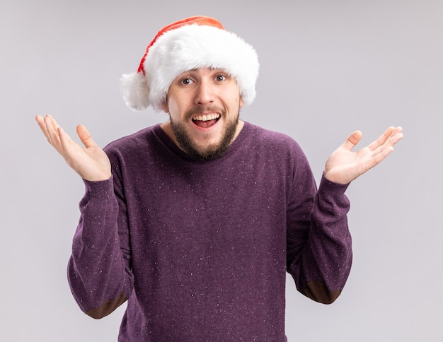 Young man in purple sweater and santa hat looking at camera smiling confused spreading arms to the sides standing over white background