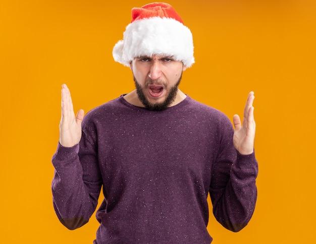 Giovane uomo in maglione viola e cappello da babbo natale che guarda l'obbiettivo con espressione infastidita con le braccia alzate in piedi su sfondo arancione
