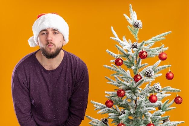 Giovane uomo in maglione viola e cappello santa cercando stanco e annoiato in piedi accanto all'albero di natale su sfondo arancione