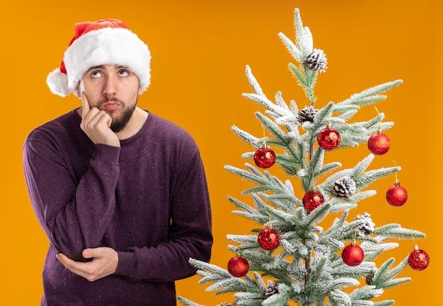 Giovane uomo in maglione viola e cappello da babbo natale alzando perplesso in piedi accanto all'albero di natale su sfondo arancione