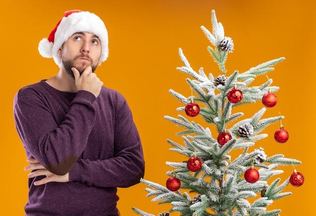 Giovane uomo in maglione viola e cappello da babbo natale guardando con espressione pensierosa sul viso pensando accanto all'albero di natale su sfondo arancione