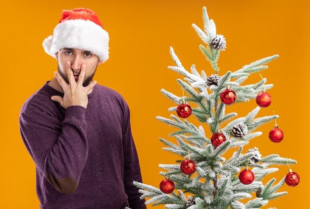 Giovane uomo in maglione viola e cappello da babbo natale tirando gli occhi verso il basso con le dita stanche e annoiate in piedi accanto all'albero di natale sul muro arancione