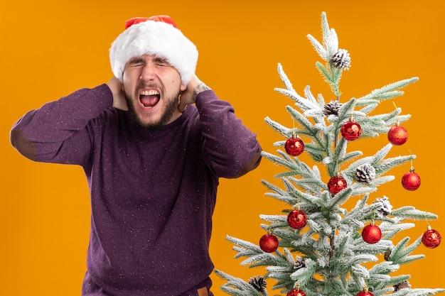 Giovane uomo in maglione viola e cappello da babbo natale che grida con espressione infastidita in piedi accanto all'albero di natale su sfondo arancione
