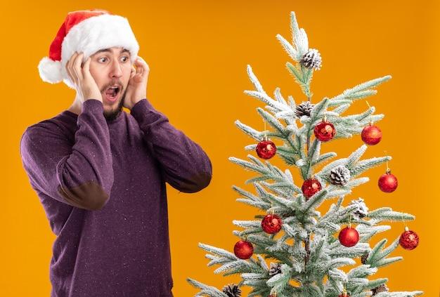 Giovane uomo in maglione viola e cappello santa in piedi accanto all'albero di natale guardando albero stupito e sorpreso su sfondo arancione