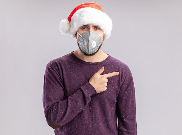 Giovane uomo in maglione viola e cappello da babbo natale che indossa una protezione facciale che guarda l'obbiettivo con faccia seria che punta con il dito indice a lato in piedi su sfondo bianco