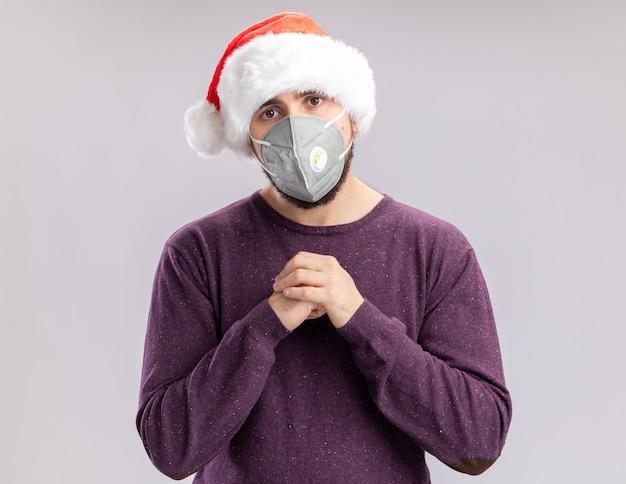 Giovane uomo in maglione viola e cappello da babbo natale che indossa la maschera protettiva per il viso tenendosi per mano insieme guardando la fotocamera stanco e annoiato in piedi su sfondo bianco